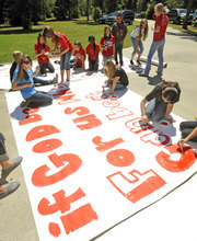 FILE - In this Sept. 19, 2012 file photo, Kountze High School cheerleaders and other children work on a large sign in Kountze, Texas.  Texas Attorney General Greg Abbott announced Wednesday that he is intervening in a lawsuit that cheerleaders filed against the school district. The district told the cheerleaders to stop using Bible verses at football games after the Freedom From Religion Foundation complained. (AP Photo/The Beaumont Enterprise, Dave Ryan, File)