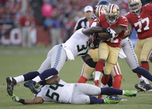 San Francisco 49ers running back Kendall Hunter (32) is tackled by Seattle Seahawks strong safety Kam Chancellor (31) during the first half of an NFL football game in San Francisco, Thursday, Oct. 18, 2012. (AP Photo/Ben Margot)