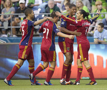Real Salt Lake's Fabian Espi ́ndola, far right, celebrates scoring a goal with teammates, from left, Alvaro Saborio, Luis Gil and Chris Schuler during the second half of play in a MLS soccer match, Saturday, May 12, 2012, in Seattle. Real Salt Lake won the match 1-0. (AP PHOTO/Stephen Brashear)