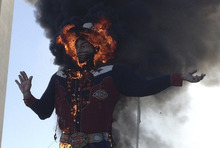 Fire engulfs the Big Tex cowboy statue displayed at the State Fair of Texas in Dallas on Friday, Oct. 19, 2012. The iconic structure caught fire and burned this morning. (AP Photo/John McKibben)