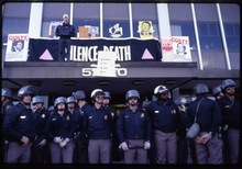|  Sundance Selects Activist Peter Staley stands on a doorway overhang at an FDA office, with riot police standing guard below, in a late '80s AIDS protest shown in the documentary