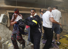 A Lebanese rescue worker, center, helps an injured man at the scene of an explosion  in the mostly Christian neighborhood of Achrafiyeh, Beirut, Lebanon, Friday Oct. 19, 2012. A car bomb ripped through eastern Beirut on Friday, shearing the balconies of off residential buildings and sending bloodied victims pouring out into the streets in the most serious blast this city has seen in years. (AP Photo/Hussein Malla)