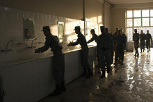 In this Tuesday, Oct. 9, 2012 photo, Afghan police officers line up to wash their hands before breakfast at the police academy in Kabul, Afghanistan. The readiness of Afghanistan's security forces is central to U.S. and NATO plans to withdraw all forces from the country by the end of 2014, and the academy's new commander wants to help turn around a 146,000-strong national police force long riddled with corruption, incompetence and factional rivalries. (AP Photo/Anja Niedringhaus)