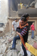 A Lebanese civilian carries an injured woman at the scene of an explosion in the mostly Christian neighborhood of Achrafiyeh, Beirut, Lebanon, Friday Oct. 19, 2012. A car bomb ripped through eastern Beirut on Friday, shearing the balconies off residential buildings and sending bloodied victims pouring out into the streets in the most serious blast this city has seen in years.(AP Photo/Hussein Malla)