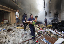 A Lebanese rescue man, carries an injured boy at the scene of an explosion in the mostly Christian neighborhood of Achrafiyeh, Beirut, Lebanon, Friday Oct. 19, 2012. A car bomb ripped through eastern Beirut on Friday, shearing the balconies of off residential buildings and sending bloodied victims pouring out into the streets in the most serious blast this city has seen in years. (AP Photo/Hussein Malla)