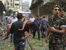 FILE - EDS NOTE: GRAPHIC CONTENT - A Lebanese civilian carries an injured girl at the scene of an explosion in the mostly Christian neighborhood of Achrafiyeh, Beirut, Lebanon, Friday Oct. 19, 2012. Lebanon's state news agency says a car bomb in east Beirut has killed at least six people and wounded scores in the worst blast the city has seen in years coming at a time when Lebanon has seen a rise in tension and eruptions of clashes stemming from the civil war in neighboring Syria. (AP Photo/Hussein Malla)