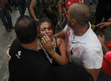 A injured woman is carried by civilians away from the scene of an explosion in the mostly Christian neighborhood of Achrafiyeh, Beirut, Lebanon, Friday Oct. 19, 2012.  Lebanese Red Cross and security officials say a car bomb in east Beirut has killed at least eight people and wounded dozens in the worst blast the city has seen in years, coming at a time when Lebanon has seen a rise in tension and eruptions of clashes stemming from the civil war in neighboring Syria. (AP Photo/Hussein Malla)