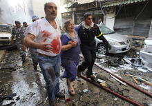 A Lebanese rescue worker, right, helps injured people to leave the scene of an explosion in the mostly Christian neighborhood of Achrafiyeh, Beirut, Lebanon, Friday Oct. 19, 2012. Lebanese Red Cross and security officials say a car bomb in east Beirut has killed at least eight people and wounded dozens in the worst blast the city has seen in years, coming at a time when Lebanon has seen a rise in tension and eruptions of clashes stemming from the civil war in neighboring Syria. (AP Photo/Hussein Malla)