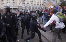 File - In this Sept. 25, 2012 file photo, a police officer hits a man with a baton during a march to the parliament against austerity measures announced by the Spanish government, in Madrid. Spain's government said Friday Oct. 19, 2012 it is considering a ban on photographing, filming and reproducing images of police and state security forces while