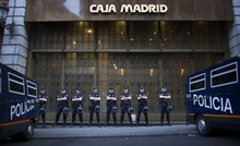 File - In this May 14, 2012 file photo, riot police stand guard in front of a branch of the recently nationalized Caja de Madrid/ Bankia bank in Madrid. Spain's government said Friday Oct. 19, 2012 it is considering a ban on photographing, filming and reproducing images of police and state security forces while