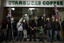 Demonstrators stand outside a branch of Starbucks as they gather near St Paul's Cathedral before the start of an anti-austerity protest march through central London, Saturday, Oct. 20, 2012.  Tens of thousands of demonstrators are descending on the British capital to protest the government's austerity drive.  Unions, anti-war campaigners, left-wing politicians, community groups and other activists hope that Saturday's march will show the unpopularity of the public sector cuts aimed at reining in Britain's budget deficit.  (AP Photo/Matt Dunham)