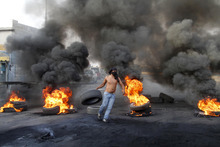 A masked protester carried a tire to add to burning tires used as a roadblock to protest the death of Brig. Gen. Wissam al-Hassan, head of the intelligence division of Lebanon's domestic security forces in a car bomb attack targeting his convoy, in the southern port city of Sidon, Lebanon, Saturday, Oct. 20, 2012. Protesters burned tires and set up roadblocks around Lebanon on Saturday in a sign of boiling anger over a massive car bomb that killed a top security official and seven other people a day earlier — a devastating attack that threatened to bring Syria's civil war to Lebanon.(AP Photo/ Mohammed Zaatari)