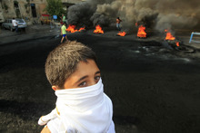 A masked Lebanese youth stands near flaming tires used as a roadblock to protest the death of Brig. Gen. Wissam al-Hassan, head of the intelligence division of Lebanon's domestic security forces in a car bomb attack targeting his convoy, in the southern port city of Sidon, Lebanon, Saturday, Oct. 20, 2012. Protesters burned tires and set up roadblocks around Lebanon on Saturday in a sign of boiling anger over a massive car bomb that killed a top security official and seven other people a day earlier — a devastating attack that threatened to bring Syria's civil war to Lebanon.(AP Photo/ Mohammed Zaatari)