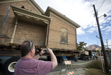 Lennie Mahler  |  The Salt Lake Tribune Local resident John Hopkins snaps a photo as a truck pulls the Casto Home, weighing about 110-tons, along Laney Avenue in Holladay. Saturday, Oct. 20, 2012.