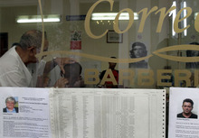An electoral roll and two candidates' resumes are taped to a barber shop's store window, in Old Havana, Cuba, earlier this month. Elections in Cuba lack the hoopla they have in other countries, but authorities here say they give people a voice in government and answer charges that the communist-run country is undemocratic. Critics call the votes, including one scheduled for Sunday, Oct. 21, 2012, a sham since voters can't throw out the Communist Party or the Castros. (AP Photo/Franklin Reyes)