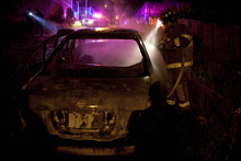 In this Sept. 18, 2012 photo, a firefighter puts out a smoldering car allegedly used in a robbery at a Coca-Cola distribution center in Morelia, Mexico. The robbers pistol-whipped three security guards, grabbed thousands of pesos in cash and fled. In cities and towns across Mexico, a nearly six-year offensive against drug cartels has been accompanied by a surge in common crime: assaults and robberies that grab no headlines but make life miserable for ordinary citizens.  (AP Photo/Alexandre Meneghini)