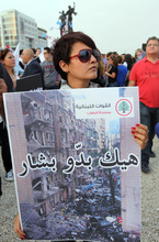 A Lebanese woman holds a poster with Arabic that reads,