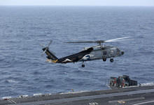A U.S. Navy SH-60 Seahawk prepares to land on the deck of the nuclear-powered USS George Washington (CVN73) off southern coast of Vietnam in South China Sea Saturday, Oct. 20, 2012. A U.S. aircraft carrier group cruised through the disputed South China Sea on Saturday in a show of American power in waters that are fast becoming a focal point of Washington's strategic rivalry with Beijing. (AP Photo/Na Son Nguyen)