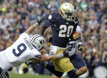 Notre Dame running back Cierre Wood, right, breaks the tackle of BYU defensive back Daniel Sorensen during the first half of an NCAA college football game in South Bend, Ind., Saturday, Oct. 20, 2012. (AP Photo/Michael Conroy)