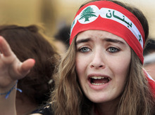 An anti Syrian regime protester reacts in Martyrs' Square for the funeral for the country's intelligence chief, Brig. Gen. Wissam al-Hassan in Beirut, Lebanon, Sunday, Oct. 21, 2012. Lebanese soldiers fired guns and tear gas to push back hundreds of protesters who broke through a police cordon and tried to storm the government headquarters in Beirut. The enraged crowd came from the funeral of a top Lebanese intelligence official assassinated in a massive car bombing. (AP Photo/Bilal Hussein)