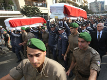 Members of Lebanese police intelligence division units carry the coffin wrapped by Lebanese flags of Brig. Gen. Wissam al-Hassan and his bodyguard who were assassinated on Friday by a car bomb, during their funeral procession at Martyrs' Square in Beirut, Lebanon, Sunday Oct. 21, 2012. Lebanese soldiers fired guns and tear gas to push back hundreds of protesters who broke through a police cordon and tried to storm the government headquarters in Beirut. The enraged crowd came from the funeral of a top Lebanese intelligence official assassinated in a massive car bombing. (AP Photo/Hussein Malla)