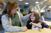 Al Hartmann  |  The Salt Lake Tribune Heather Yancery talks with her daughter Eve after having her hearing checked by an audiologist at Primary Children's Outpatient Services at Riverton Hospital Friday Ocotber 5. Loss of hearing is just one of the side-effects of her rare autoimmune disease, Cryopyrin-associated periodic syndrome (CAPS). Left untreated, the disease can cause chronic meningitis, or swelling in the brain. There's no cure, but with drugs the disease can be managed. They're expensive, though - about $20,000 a month - and getting the insurance company to pay for them is a constant struggle.
