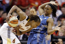 Indiana Fever forward Tamika Catchings, left, tries to make room as she is defended by Minnesota Lynx guard Monica Wright in the third quarter of Game 4 of the WNBA basketball Finals in Indianapolis, Sunday, Oct. 21, 2012. (AP Photo/Michael Conroy)