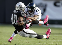 Oakland Raiders wide receiver Rod Streater (80) catches a pass against Jacksonville Jaguars cornerback Derek Cox (21) during the fourth quarter of an NFL football game in Oakland, Calif., Sunday, Oct. 21, 2012. The Raiders won 26-23 in overtime. (AP Photo/Marcio Jose Sanchez)