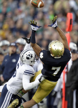 Notre Dame wide receiver TJ Jones (7) makes a catch for 31 yards as BYU defensive back Jordan Johnson defends during the second half of an NCAA college football game in South Bend, Ind., Saturday, Oct. 20, 2012. Notre Dame defeated BYU 17-14. (AP Photo/Michael Conroy)