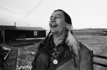 FILE - In a Feb. 4, 1974 file photo, American Indian Movement (AIM) leader Russell Means, who is challenging incumbent Oglala Sioux Tribal President Richard Wilson in Thursday's election on the Pine Ridge Indian Reservation, laughs at news report which quoted Wilson as saying he will give AIM 10 days to get off the reservation after he is reelected