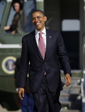 President Barack Obama smiles as he walks across the tarmac from the Marine One helicopter to Air Force One at Andrews Air Force Base, Md., Monday, Oct. 22, 2012, enroute to Boca Raton, Fla., and the last presidential debate against Republican presidential candidate, former Massachusetts Gov. Mitt Romney. (AP Photo/Pablo Martinez Monsivais)