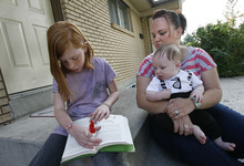 Scott Sommerdorf  |  The Salt Lake Tribune               Nina Neubert listens as her daughter Jasmyn Neubert, 9, reads a book after school, while holding her 4-month-old son, Jaiden, on the front porch of their Orem home, Friday, October 19, 2012. Neubert says she was misled about the adoption process by DCFS, causing her to lose the opportunity to adopt her nieces and nephew from foster care due to a missed deadline. The children will likely now be adopted by a foster family.