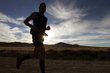 Al Hartmann  |  The Salt Lake Tribune A runner breaks through the shadows as the sun rises in the early miles of the Pony Express Trail 100 Endurance Run Friday, Oct. 19.   Some 75 entrants and their support teams will run the 50-mile course or the 100-mile course along the historic Pony Express route in the west desert areas of Tooele and Juab counties.