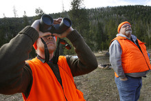 Scott Sommerdorf  |  The Salt Lake Tribune               Nicholas Smith, left, scans the hillsides near Kamas for deer as Shawn Gehring, right, looks on, Saturday, October 20, 2012. The general season rifle deer hunt opened at dawn Saturday with a new format that limits hunters to one of 30 units instead of one of five regions in the state. More than 52,000 are expected to be in the field.