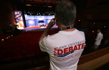 Lynn University alum and Board of Trustees member John Langan takes a photo of the stage during final preparations for Monday's presidential debate between President Barack Obama and Republican presidential candidate, former Massachusetts Gov. Mitt Romney, Sunday, Oct. 21, 2012, at Lynn University in Boca Raton, Fla. (AP Photo/Charlie Neibergall)