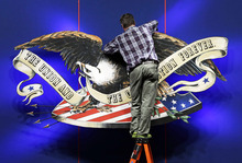 A worker adjusts the backdrop on stage in preparation for Monday's presidential debate between President Barack Obama and Republican presidential candidate, former Massachusetts Gov. Mitt Romney, Sunday, Oct. 21, 2012, at Lynn University in Boca Raton, Fla. (AP Photo/Charlie Neibergall)