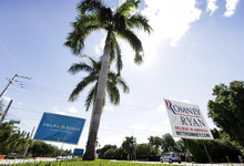 Campaign igns are seen in a median in front of Lynn University, site of Monday's presidential debate between President Barack Obama and Republican presidential candidate, former Massachusetts Gov. Mitt Romney, Sunday, Oct. 21, 2012, in Boca Raton, Fla. (AP Photo/Charlie Neibergall)