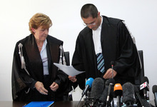 Judge Marco Billi, right, flanked by court clerk Patrizia Cripoli reads the verdict at L'Aquila court, Italy, Monday, Oct. 22, 2012. An Italian court has convicted seven scientists and experts of manslaughter for failing to adequately warn citizens before an earthquake struck central Italy in 2009, killing more than 300 people. The court in L'Aquila Monday evening handed down the convictions and six-year-prison sentences to the defendants, members of a national