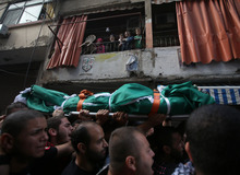 A Palestinian family, top, look at mourners carrying the body of Palestinian Ahmad Queider, 20, who was killed Monday as he rode his motorcycle, during an exchange of gunfire between Lebanese troops and gunmen, during the funeral procession, in the Sunni neighborhood of Tarik al-Jadida, Beirut, Lebanon, Tuesday Oct. 23, 2012. Gunmen fired heavily in the air as hundreds of people marched behind the body draped in green and carried on a stretcher toward the cemetery for burial. Calm returned to the streets of Lebanon's capital on Tuesday, a day after troops launched a major security operation to quell fighting touched off by the assassination of a top anti-Syrian intelligence chief.(AP Photo/Hussein Malla)