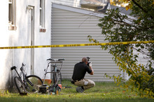 An investigators photographs evidence in the back yard of a house on Clayton Avenue in Clayton NJ on Tuesday Oct. 23, 2012, after the discovery of a girl's body in a home's recycling bin. Gloucester County prosecutors say a body believed to be that of Autumn Pasquale was found around 10 p.m. Monday in the bin just blocks from her house and from Borough Hall, where thousands of people gathered earlier in the evening for a tearful candlelight vigil to pray for her safe return.  (AP Photo/ Joseph Kaczmarek)