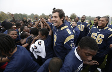 St. Louis Rams quarterback Sam Bradford reacts with school children as he takes part in a NFL organised coaching session for some London schoolchildren in Regents Park, London, Tuesday, Oct. 23, 2012. The Rams are to play the New England Patriots at Wembley stadium in London, Sunday, Oct. 28 in a regular season game. (AP Photo/Alastair Grant)