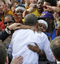 President Barack Obama is embraced by a unidentified supporter during a campaign event at Triangle Park in Dayton, Ohio, Tuesday, Oct. 23, 2012, the day after the last presidential debate against Republican Presidential candidate, former Massachusetts Gov. Mitt Romney. (AP Photo/Pablo Martinez Monsivais)