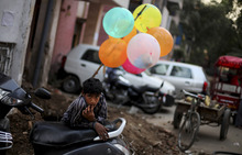 A young balloon seller leans on a parked scooter as he waits for customers near a fair ground in New Delhi, India, Tuesday, Oct. 23, 2012. (AP Photo/Altaf Qadri)