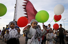 Palestinian children wave colored balloons and Qatari flags while waiting for the convoy of Emir of Qatar Sheikh Hamad bin Khalifa al-Thani, not pictured, to pass by a street in Gaza City, Tuesday, Oct. 23, 2012. The emir of Qatar received a hero's welcome in Gaza on Tuesday, becoming the first head of state to visit the Palestinian territory since the Islamist militant Hamas seized control there in 2007. (AP Photo/Hatem Moussa)
