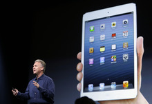 Phil Schiller, Apple's senior vice president of worldwide product marketing, talks in front of a projection of the iPad mini in San Jose, Calif., Tuesday, Oct.  23, 2012.  Apple Inc. is refusing to compete on price with its rivals in the tablet market  it's pricing its new, smaller iPad well above the competition. On Tuesday, the company revealed the iPad Mini, with a screen that's about two-thirds the size of the full-size model, and said it will cost $329 and up. (AP Photo/Marcio Jose Sanchez)