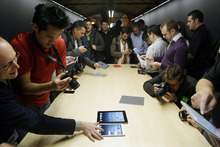 The iPad Mini is examined in San Jose, Calif., Tuesday, Oct.  23, 2012.  Apple Inc. is refusing to compete on price with its rivals in the tablet market, it's pricing its new, smaller iPad well above the competition. On Tuesday, the company revealed the iPad Mini, with a screen that's about two-thirds the size of the full-size model, and said it will cost $329 and up. (AP Photo/Marcio Jose Sanchez)