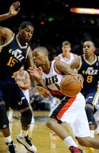 Utah Jazz' Derrick Favors (15) and Randy Foye (8) defend against a drive by Portland Trail Blazers' Damian Lillard (0) during the second half of an NBA preseason basketball game in Portland, Ore., Monday, Oct., 22, 2012. Lillard had 21 points as the Trail Blazers beat the Jazz 120-114. (AP Photo/Greg Wahl-Stephens)