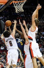 Utah Jazz's DeMarre Carroll shoots against Portland Trail Blazers' Adam Morrison (6), Meyers Leonard, right, and Joel Freeland during the first half of an NBA preseason basketball game in Portland, Ore., Monday, Oct., 22, 2012. (AP Photo/Greg Wahl-Stephens)
