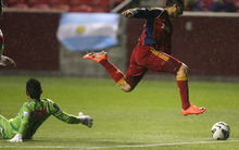 Steve Griffin | The Salt Lake Tribune   Real Salt Lake's Fabian Espindola leaps over C.S. Herediano goal keeper Leo Moreira as he chases down the ball during first half action of the their CONCACAF match at Rio TInto Stadium in Sandy, Utah Tuesday October 23, 2012.