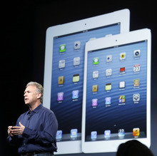 Phil Schiller, Apple's senior vice president of worldwide product marketing, speaks in front of an image of the 4th generation iPad, at left, and the iPad mini in San Jose, Calif., Tuesday, Oct.  23, 2012.  The iPad has a screen that's about two-thirds the size of the full-size model, and Apple says it will cost $329 and up.  (AP Photo/Marcio Jose Sanchez)